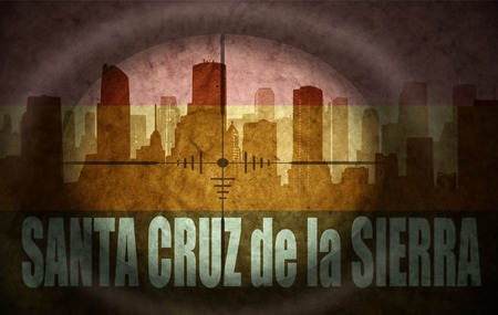 the name of the drug: sniper scope aimed at the abstract silhouette of the city with text Santa Cruz de la Sierra at the vintage bolivian flag. concept