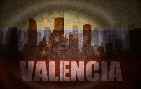 the name of the drug: sniper scope aimed at the abstract silhouette of the city with text Valencia at the vintage venezuelan flag. concept Stock Photo