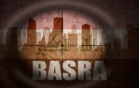 sniper scope aimed at the abstract silhouette of the city with text Basra at the vintage iraqi flag. concept