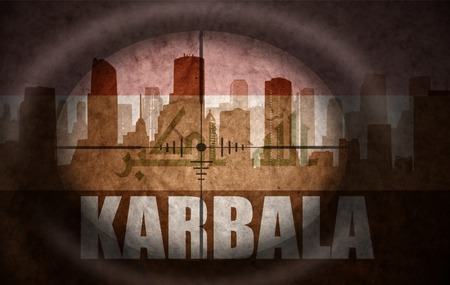iraqi: sniper scope aimed at the abstract silhouette of the city with text Karbala at the vintage iraqi flag. concept