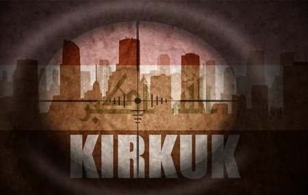 iraqi: sniper scope aimed at the abstract silhouette of the city with text Kirkuk at the vintage iraqi flag. concept Stock Photo