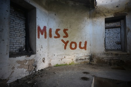 dirtiness: text miss you on the dirty old wall in an abandoned ruined house