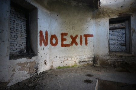 opiate: text no exit  on the dirty old wall in an abandoned ruined house Stock Photo