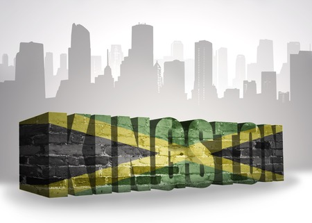 kingston: text kingston with national flag of jamaica near abstract silhouette of the city