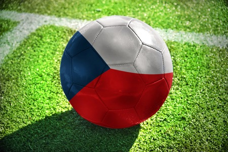football ball with the national flag of czech republic lies on the green field near the white line