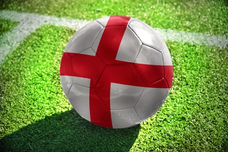 winning pitch: football ball with the national flag of england lies on the green field near the white line Stock Photo