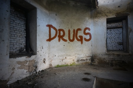 dirtiness: text drugs on the dirty old wall in an abandoned ruined house Stock Photo