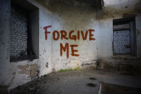 dirtiness: text forgive me on the dirty old wall in an abandoned ruined house