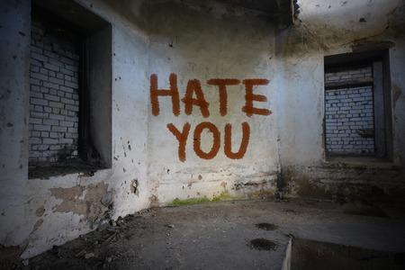 dirtiness: text hate you on the dirty old wall in an abandoned ruined house Stock Photo