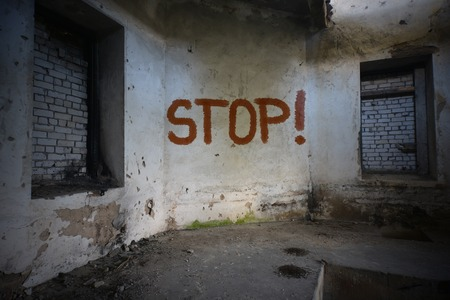 dirtiness: text stop on the dirty old wall in an abandoned ruined house
