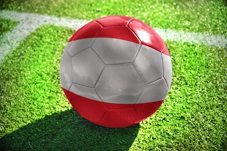 winning pitch: football ball with the national flag of austria lies on the green field near the white line Stock Photo