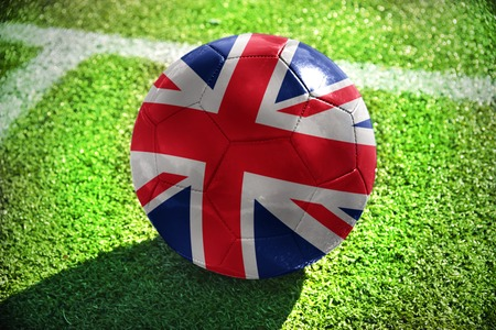winning pitch: football ball with the national flag of great britain lies on the green field near the white line