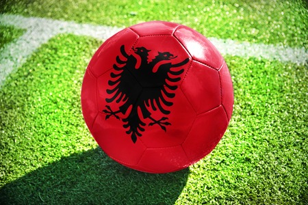 winning pitch: football ball with the national flag of albania lies on the green field near the white line