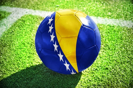 winning pitch: football ball with the national flag of bosnia and herzegovina lies on the green field near the white line