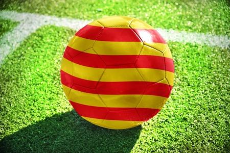 zakelijk: voetbal bal met de nationale vlag van Catalonië ligt op het groene veld in de buurt van de witte lijn