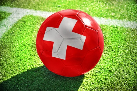 winning pitch: football ball with the national flag of switzerland lies on the green field near the white line