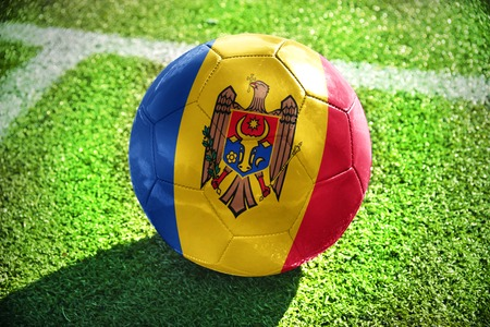 winning pitch: football ball with the national flag of moldova lies on the green field near the white line