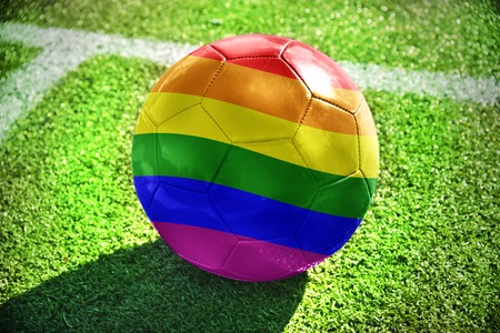 football ball with rainbow flag lies on the green field near the white line Stock fotó