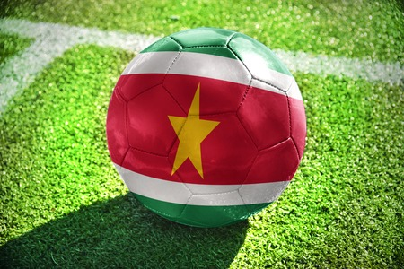 winning pitch: football ball with the national flag of suriname lies on the green field near the white line Stock Photo