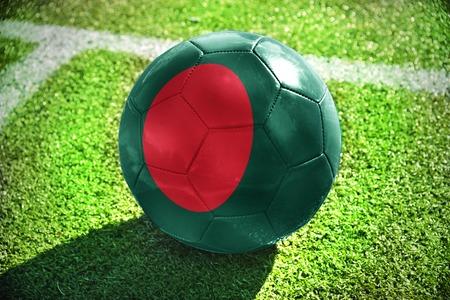 national flag bangladesh: football ball with the national flag of bangladesh lies on the green field near the white line Stock Photo