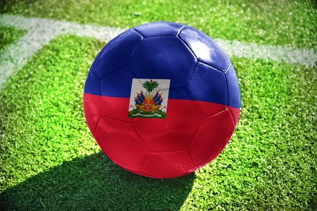 port au prince: football ball with the national flag of haiti lies on the green field near the white line