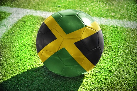 jamaica: football ball with the national flag of jamaica lies on the green field near the white line