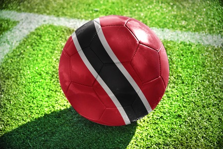 winning pitch: football ball with the national flag of trinidad and tobago lies on the green field near the white line