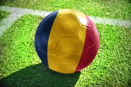 winning pitch: football ball with the national flag of chad lies on the green field near the white line Stock Photo