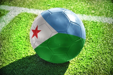 winning pitch: football ball with the national flag of djibouti lies on the green field near the white line Stock Photo
