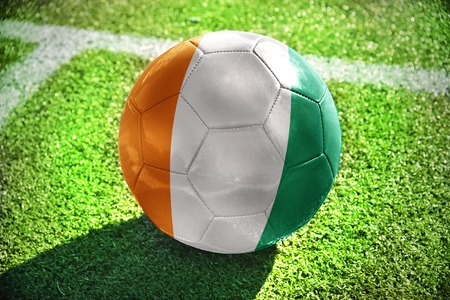 winning pitch: football ball with the national flag of cote divoire lies on the green field near the white line