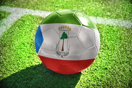 winning pitch: football ball with the national flag of equatorial guinea lies on the green field near the white line Stock Photo