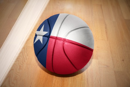 texas state flag: basketball ball with the flag of texas state lying on the floor near the white line