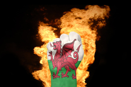 gb: fist with the national flag of wales near the fire on a black background