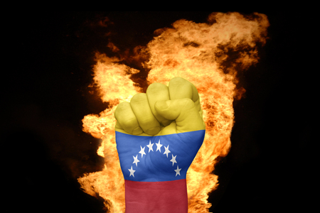 fist with the national flag of venezuela near the fire on a black background Stock Photo
