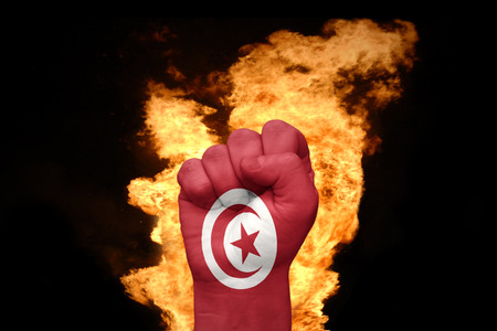 against the war: fist with the national flag of tunisia near the fire on a black background Stock Photo