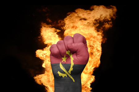 against the war: fist with the national flag of angola near the fire on a black background Stock Photo