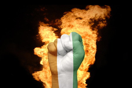 agression: fist with the national flag of cote divoire near the fire on a black background
