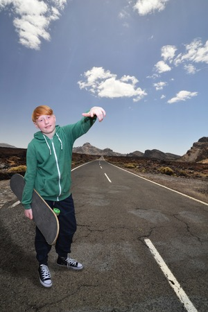 on the lonely road: young red-haired guy with skateboard standing at a lonely road