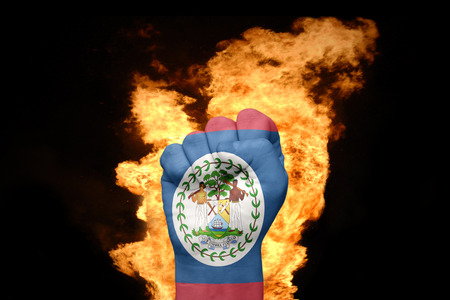 agression: fist with the national flag of belize near the fire on a black background