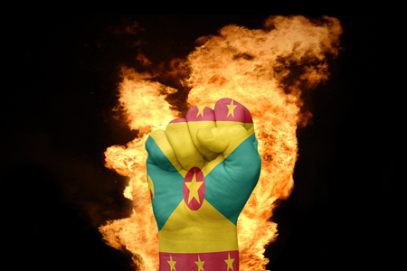agression: fist with the national flag of grenada near the fire on a black background