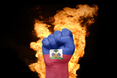 port au prince: fist with the national flag of haiti near the fire on a black background Stock Photo