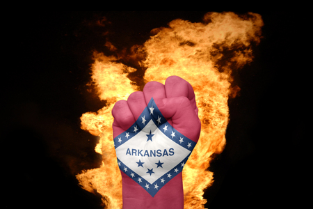 agression: fist with the flag of arkansas near the fire on a black background