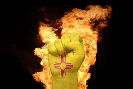 agression: fist with the flag of new mexico near the fire on a black background