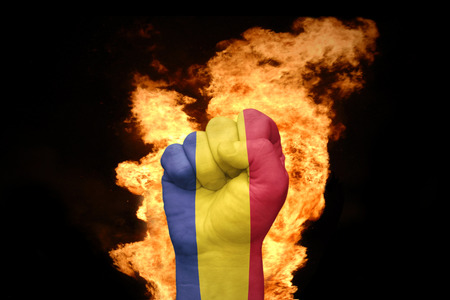 agression: fist with the national flag of chad near the fire on a black background Stock Photo