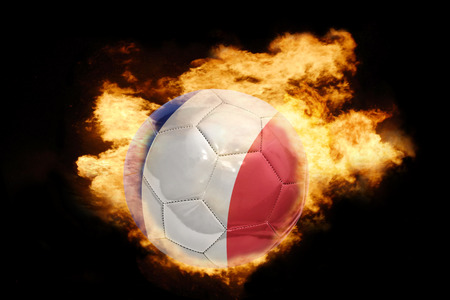 world flag: football ball with the national flag of france on fire on a black background
