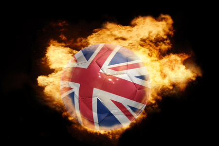 football ball with the national flag of great britain on fire on a black background