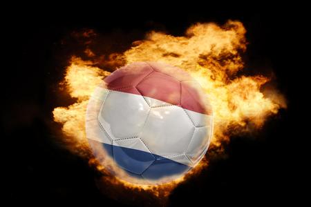bandera rusia: pelota de fútbol con la bandera nacional de los Países Bajos en el fuego sobre un fondo negro