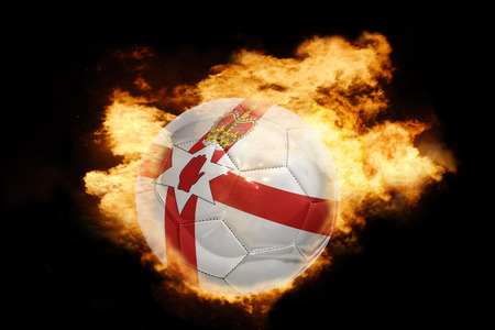 world flag: football ball with the national flag of northern ireland on fire on a black background