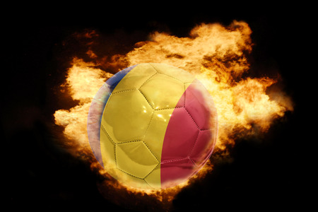football european championship: football ball with the national flag of romania on fire on a black background