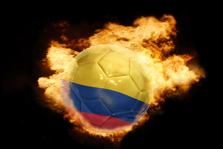 soccer world cup: football ball with the national flag of colombia on fire on a black background Stock Photo